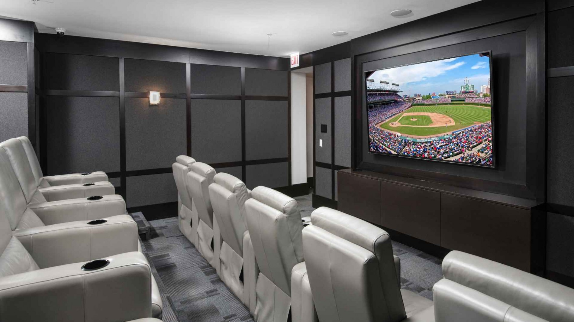 State-of-the-art movie theater with oversized screen and stadium-style leather seating.