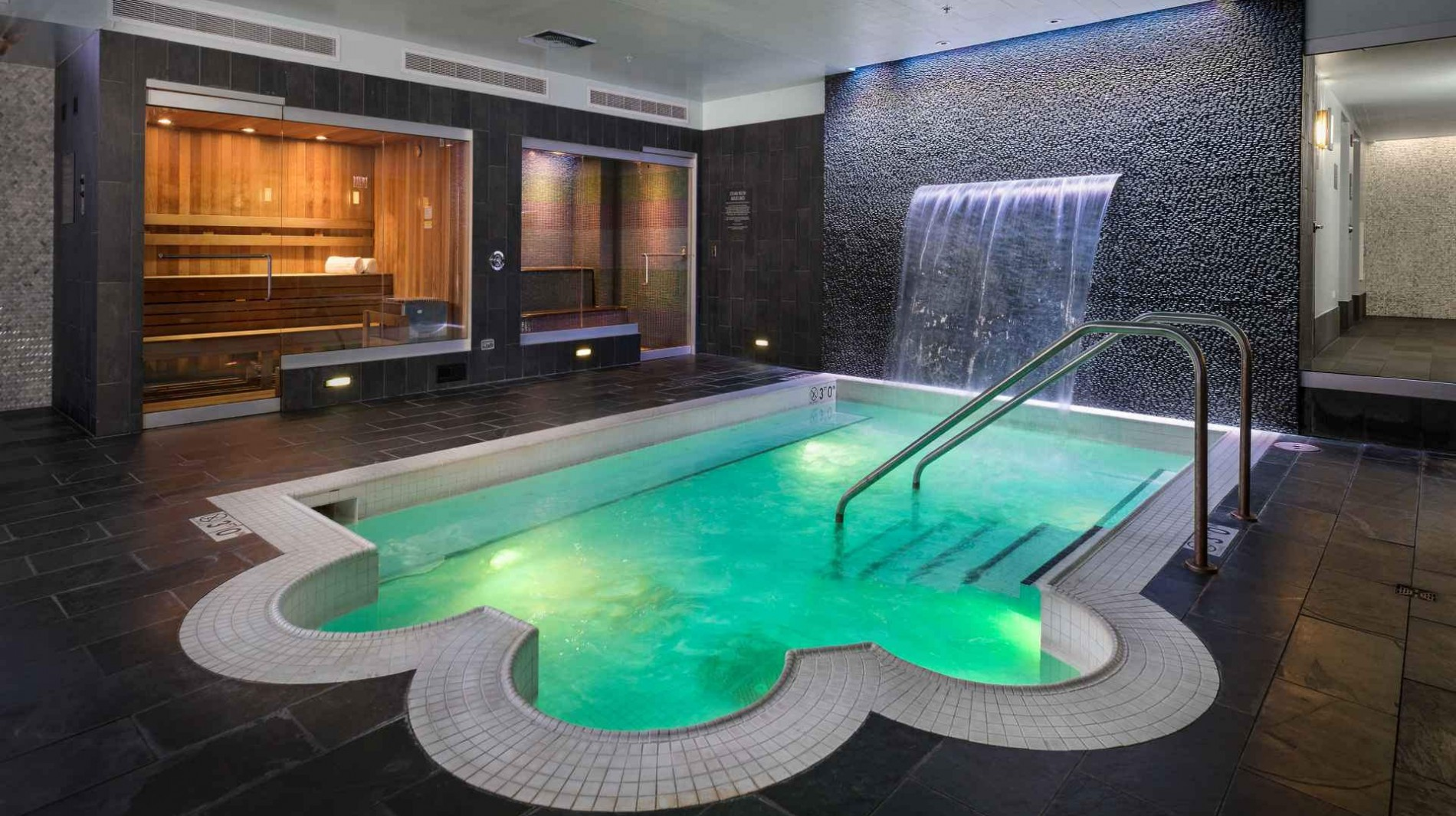 Serene indoor spa featuring indoor pool, steam room, sauna, and private massage room